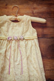 Vintage cream girl's dress on hanger with on wooden background Royalty Free Stock Image
