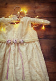 Vintage cream girl's dress on hanger with on wooden background with garland lights Royalty Free Stock Photo