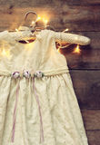 Vintage cream girl's dress on hanger with on wooden background with garland lights Royalty Free Stock Photography