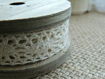 Vintage cream lace on wooden bobbin on burlap background. Vintage cream lace on old wooden bobbin on burlap background Royalty Free Stock Image