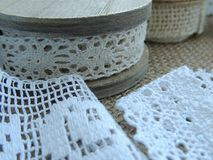 Vintage cream lace on wooden bobbin, white lace on burlap background. Vintage cream lace on old wooden bobbin, white lace on burlap background Stock Photography