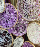 Vintage crocheted doilies in a group with stretch frames on them. Hanging on the wall Stock Photo