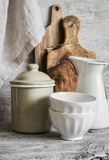 Vintage crockery and kitchen utensils - ceramic bowls, enamelled jug and container, cutting boards olive Stock Photo