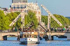 A vintage cruise boat passes the famous Amsterdam Skinny Bridge Stock Images