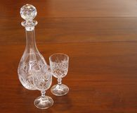 Cut-glass crystal decanter and goblet wine glasses on mahogany dining table royalty free stock photography