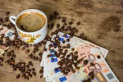 Vintage cup of black coffee and euro banknotes Stock Images