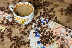 Vintage cup of black coffee and euro banknotes Stock Image