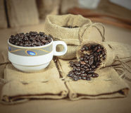 Vintage cup of roasted coffee beans on sack surface. Soft focus Stock Image