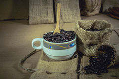 Vintage cup of roasted coffee beans on sack surface. Vintage cup of roasted coffee beans on sack surface, Soft focus Royalty Free Stock Photography