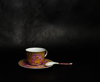 Vintage cup, saucer and spoon. On a black background Royalty Free Stock Image