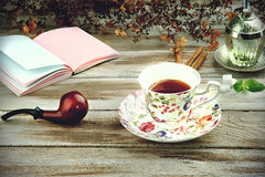 Vintage cup with smoking pipe and notebook Royalty Free Stock Image