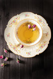 Vintage cup of tea with rosebuds, on black background Royalty Free Stock Images