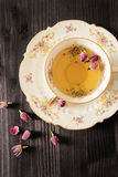 Vintage cup of tea with rosebuds, on black background Royalty Free Stock Image