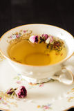 Vintage cup of tea with rosebuds, on black background Stock Photo