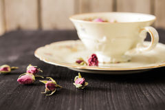 Vintage cup of tea with rosebuds, on black background Stock Image