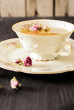 Vintage cup of tea with rosebuds, on black background Stock Photos