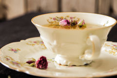 Vintage cup of tea with rosebuds, on black background Stock Images