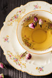 Vintage cup of tea with rosebuds, on black background Royalty Free Stock Photo