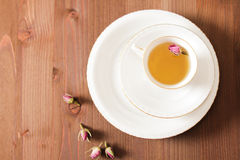 Vintage cup of tea with rosebuds,on brown background Royalty Free Stock Photos