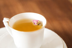 Vintage cup of tea with rosebuds,on brown background Stock Image