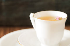 Vintage cup of tea with rosebuds,on brown background Stock Images