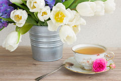 Vintage cup of tea with tulips Royalty Free Stock Photos