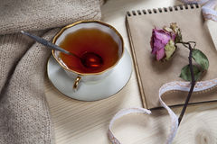 The Vintage cup of tea wrapped in a woolen plaid and pad with a dry rose on the table Royalty Free Stock Images
