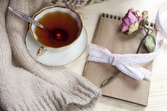 The Vintage cup of tea wrapped in a woolen plaid and pad with a dry rose on the table Royalty Free Stock Photo