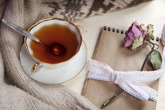The Vintage cup of tea wrapped in a woolen plaid and pad with a dry rose on the table Stock Photos