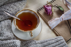 The Vintage cup of tea wrapped in a woolen plaid and pad with a dry rose on the table Royalty Free Stock Photos
