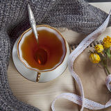 The Vintage cup of tea wrapped in a woolen plaid and pad with a dry rose on the table Stock Photo