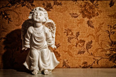 Vintage cupid sculpture. With floral background Stock Images