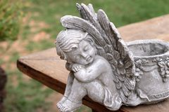 Vintage cupid sculpture on wood background.  Royalty Free Stock Photography