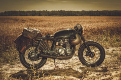 The vintage custom cafe racer in a field. Royalty Free Stock Images