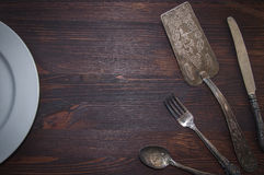 Vintage cutlery on brown wooden surface Stock Photos