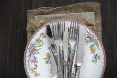 Vintage cutlery and crockery on cloths on rustic wooden backgrou Stock Image