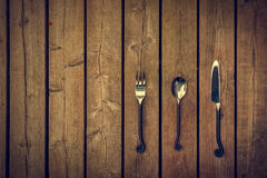 Vintage Cutlery - Fork, Spoon and Knife on Wood Background Stock Photos