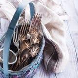 Vintage cutlery in old blue wicker basket Stock Images