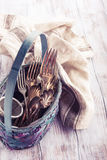 Vintage cutlery in old blue wicker basket Royalty Free Stock Photo