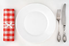 Vintage cutlery set with fork, knife, plate and red checkered napkin. Stock Photo