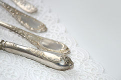 Vintage cutlery on white lace Royalty Free Stock Image