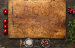 Vintage cutting board with cherry tomatoes, herbs and spices place for text  wooden rustic background top view close up Royalty Free Stock Images