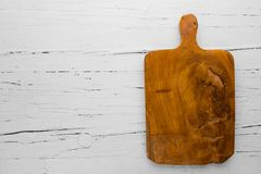 Vintage cutting board with copy space on white wooden background. View from above royalty free stock photo