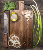 Vintage cutting board with ingredients for cooking, garlic, onion rings, green onions Oil knife place for text,frame on wooden stock photography