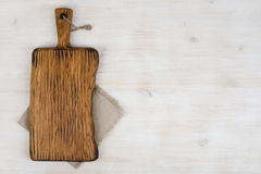 Vintage cutting board with linen napkin on wooden texture background royalty free stock photo