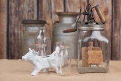 Vintage dairy tools. Vintage butter churn, glass milk bottles and cow creamer.  Old milk cans are in the background Stock Photo