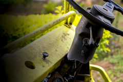 A vintage damage old car wheel and key slot, The wheel and the key shown on yellow green plant background. Stock Photos