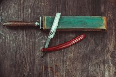 Vintage dangerous razor with leather sharpener. On a wooden background Royalty Free Stock Images