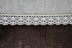 Vintage dark wood wooden desk and white lacy ribbon canvas textile background. Photo royalty free stock images