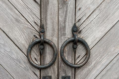Vintage dark wooden gates with round metal handles in the form of rings. Background. Stock Image